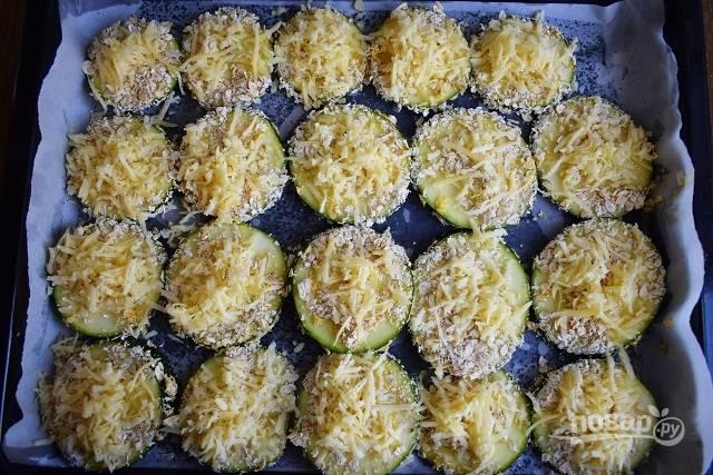 На противень положите пергамент, слегка смажьте его маслом. Колечки кабачка окуните сначала во взбитые яйца, а затем в панировку из овсяных хлопьев. Выкладывайте кружочки на пергамент, сверху присыпьте тертым сыром.