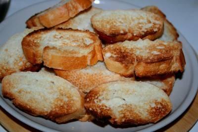 Багет нарезаем одинаковыми не очень толстыми ломтиками и обжариваем на сухой сковородке с двух сторон.