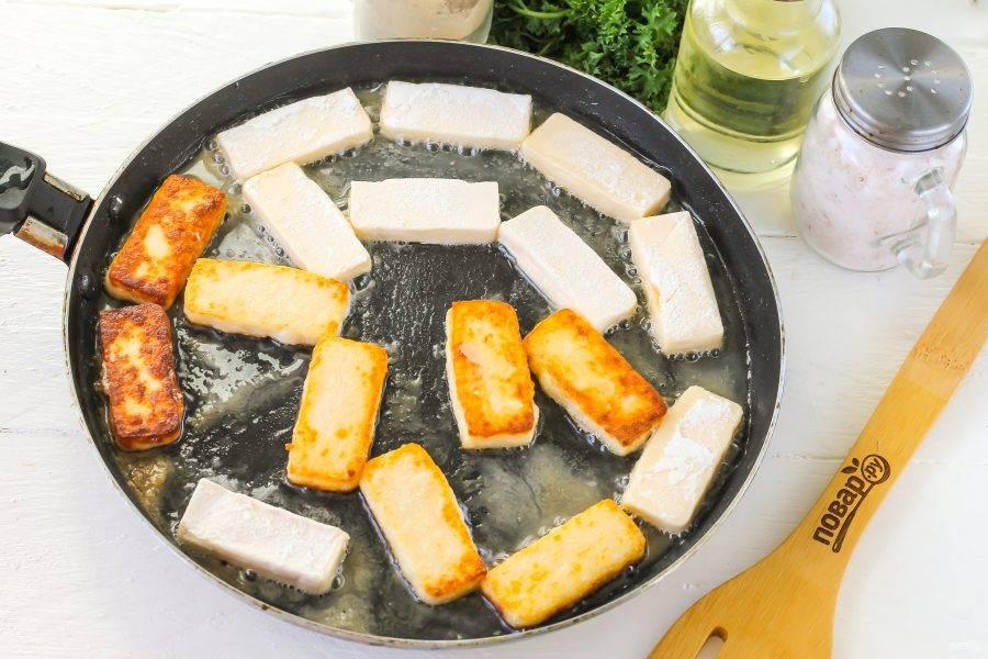 Разогрейте на сковороде растительное масло без запаха, убавьте нагрев до минимального. Выложите ломтики сыра и обжарьте их с каждой стороны по 1-2 минуте.