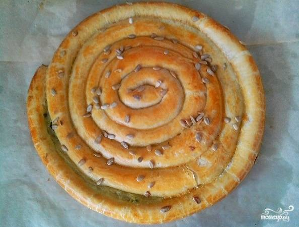 8. Смажьте верх пирога взбитым желтком, присыпьте по желанию семенами льна, кунжута, подсолнечника. Отправьте в разогретую до 190 градусов духовку. Выпекается пирог около получаса. Но следите, пока не появится румяная корочка.