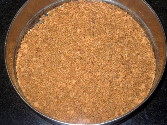 Затем нужно поломать печенье, лучше всего это делать в целлофановом пакете. Его нужно измельчить в крошку, в принципе, для этого дела отлично подойдёт и блендер. В отдельной миске смешайте крошки печенья с какао-порошком. Аккуратно перемешайте.