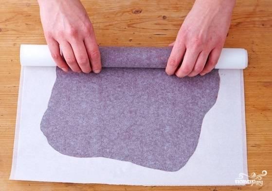 10. Сверху накройте вторым листом и разровняйте шоколад скалкой. Аккуратно сверните пергамент трубочкой и закрепите резинкой. Отправьте в морозилку минимум на 1-1.5 часа.