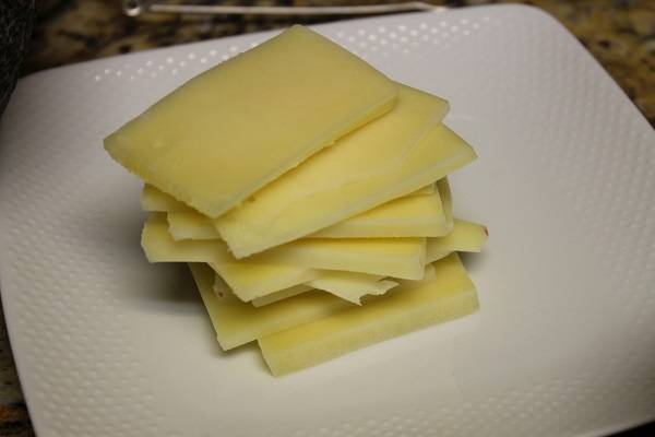 3. Для сочности и дополнительной пикантности в рецепт приготовления запеченной курицы с грибами можно использовать твердый сыр, который нужно нарезать не очень тонкими пластинками.