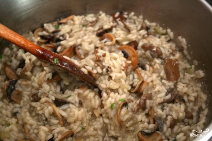 Когда рис будет готов, добавьте в кастрюлю прожаренные грибы, перемешайте, добавьте 25 грамм сливочного масла и посыпьте тертым пармезаном.