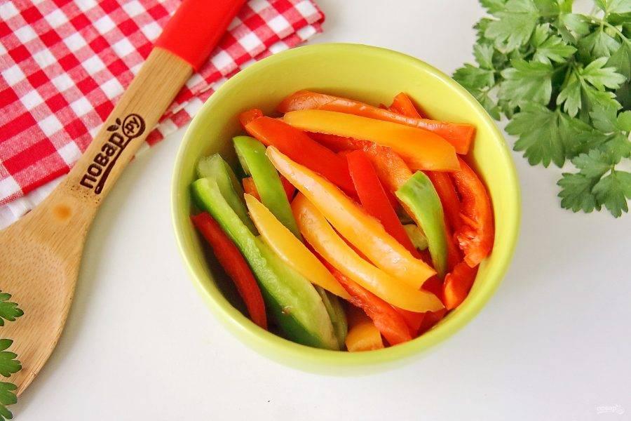 Болгарский перец очистите от семян, промойте и нарежьте соломкой.