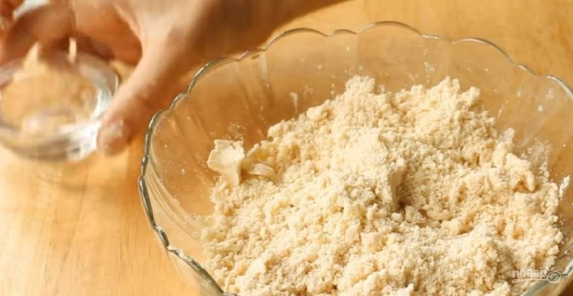 1. Муку перетрите с холодным сливочным маслом до состояния мелкой крошки. Добавьте холодную воду и замесите тугое тесто. Заверните тесто в пленку и отправьте в холодильник на 30 минут.