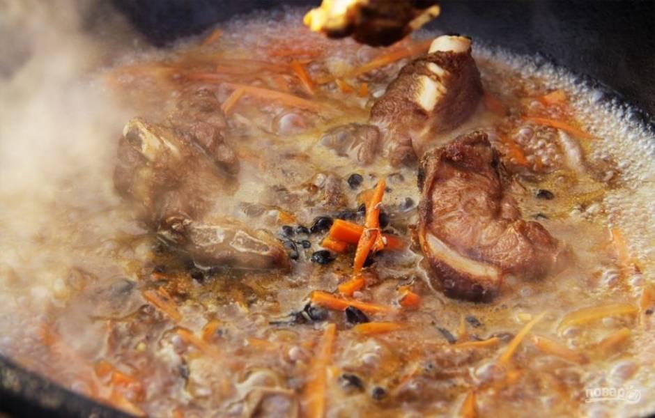 Добавьте в казан обжаренные кости, зиру, соль и барбарис.