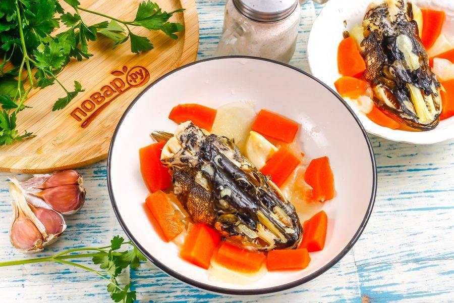 Извлеките головы щуки из бульона и поместите в середину глубоких тарелок. Выложите туда же отварные овощи. Можно дополнить их отварным куриным яйцом, очищенным от скорлупы и нарезанным на ломтики.
