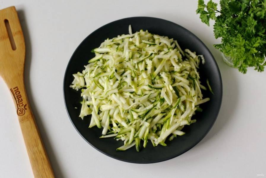 Кабачок натрите на крупной терке, добавьте щепотку соли и перемешайте. Оставьте на 5 минут, чтобы он пустил сок.