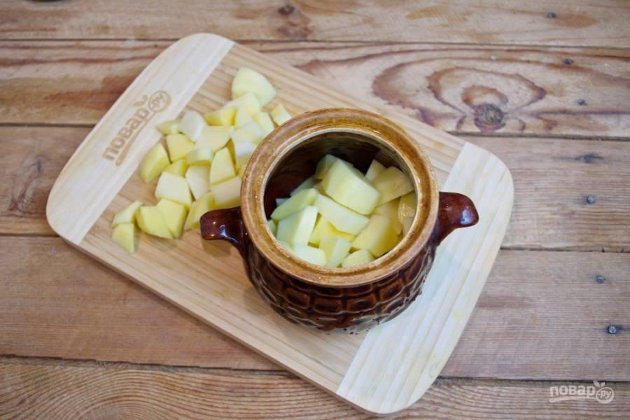 В горшочек поместите немного картофеля (до половины горшочка).