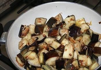 Баклажаны кладем в миску с подсоленной водой на 15 минут, чтобы вышла вся горечь. На растительном масле обжариваем лук до золотистости, затем добавляем баклажаны (обсушенные) и жарим до румяности.