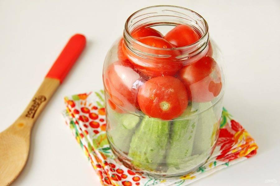 Вертикально поставьте в банки огурчики в один слой. Затем наполните банки до верха помидорами.