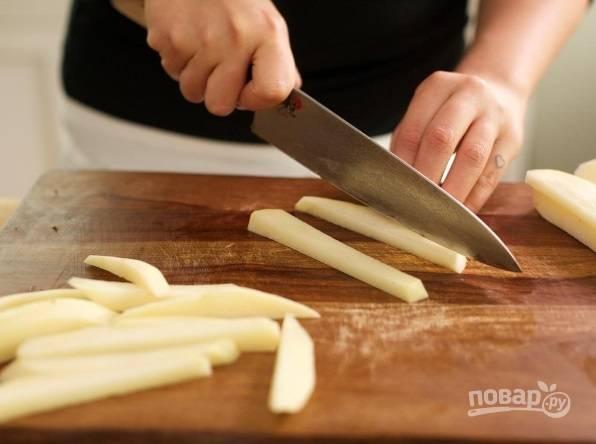 Очищенный и промытый картофель нарежьте длинными ломтиками. Затем выложите их в воду, чтобы ушёл крахмал.