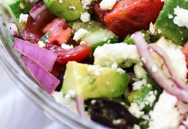 4. Полейте заправкой салат, аккуратно его перемешайте. Добавьте в салатник авокадо и сыр Фету.