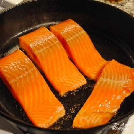 Разогреваем толстодонную сковороду. В сухую сковороду кладем кусочки рыбы, обжариваем 2 минуты с одной стороны.