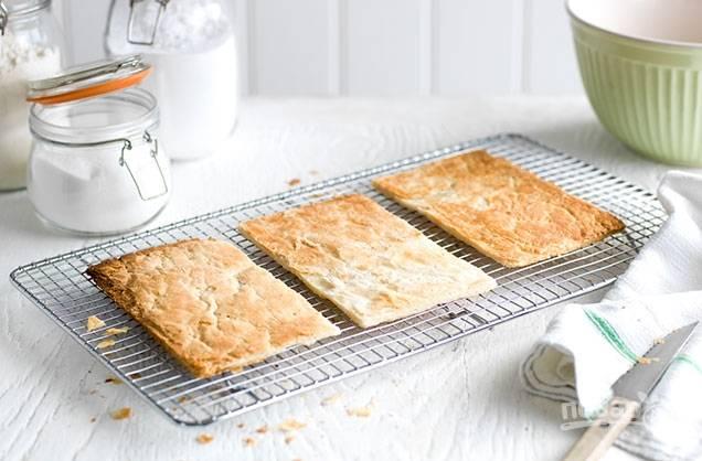 1. Разморозьте слоенное тесто, раскатайте его в прямоугольник и поделите на три части. Запекайте тесто в духовке при температуре 180 градусов 15-20 минут.