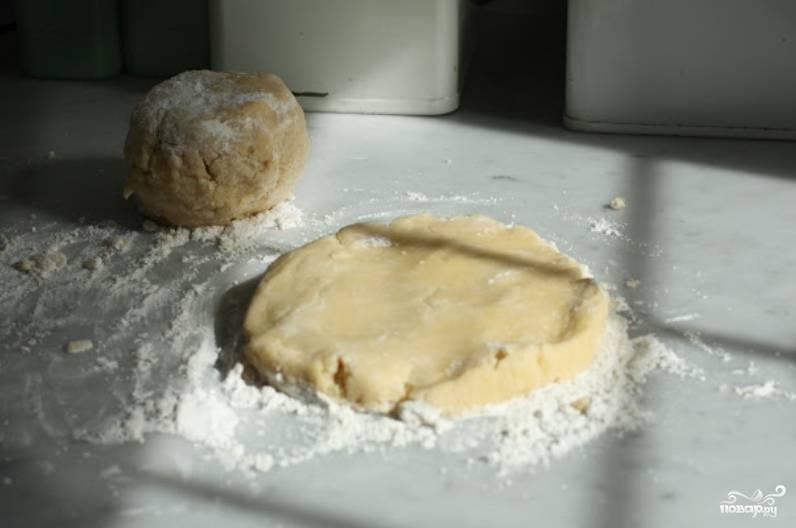 Замесите тесто и разделите на две части. Одну поместите в морозилку, а вторую раскатайте размером чуть больше формы для запекания.