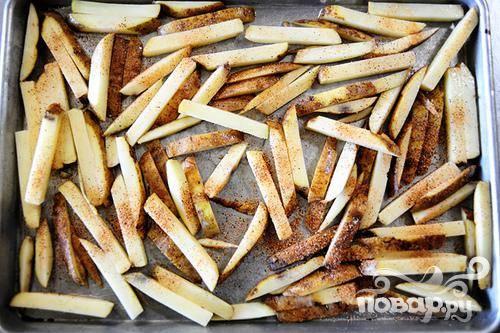 1. Разогреть духовку до 220 градусов. Мелко нарубить чеснок. Нарезать картофель на длинные тонкие ломтики. Выложить на большом листе для выпечки. Налить примерно 1 столовую ложку масла на картофель и посыпать солью и приправой для картофеля при желании. Поместить в духовку. Выпекать около 45 минут, до золотистого цвета и хрустящей корочки.