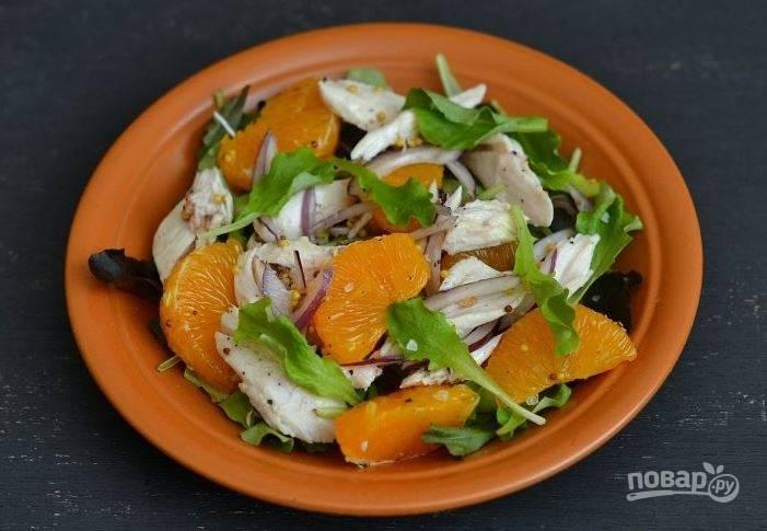 Вымойте салат и обсушите его. Выложите зелень на тарелку, в которой собираетесь подавать блюдо. Положите на листья салата курицу с луком и мандаринами, полейте заправкой и посолите по вкусу.