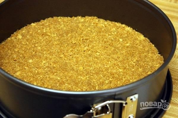 3. Добавьте растопленное сливочное масло, перемешайте. Выложите крошку в жаропрочную форму и разровняйте, чтобы получился корж.  Пока готовите начинку, отправьте форму в морозилку.