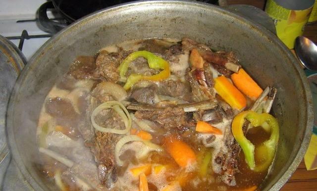 Доливаем сверху воды (чтоб чуть покрылось мясо). Добавляем порезанный помидор, морковь и картофель кубиками. Затем - лавровый лист, соль и перец по вкусу. Варим, помешивая и снимая пену. Весь процесс займет примерно 1 час.