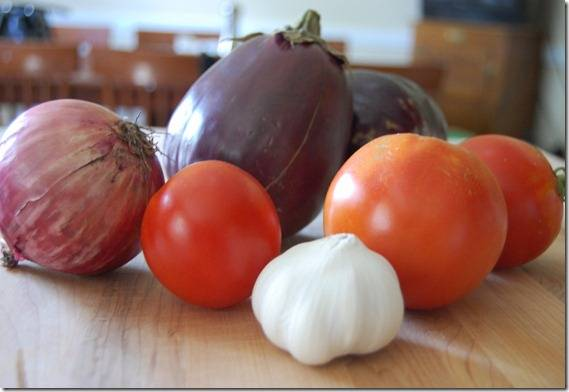 1. Включите духовку нагреваться на 180 градусов. Почистите лук и чеснок, промойте баклажан и помидоры.