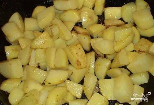 Мясо убираем со сковороды, доливаем немного растительного масла и отправляем картофель, очищенный и нарезанный кубиками. И жарим до полуготовности, периодически помешивая.