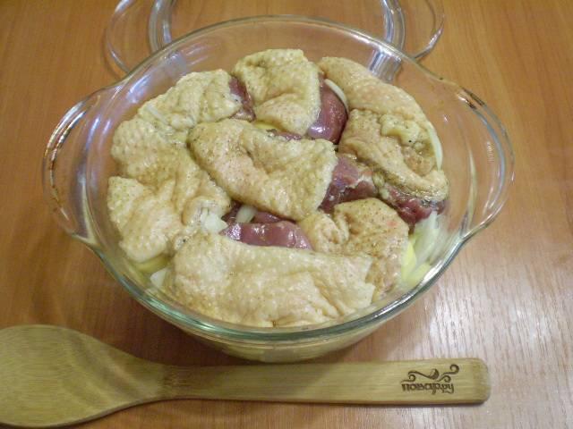 Возьмите тару для запекания. На дно уложите кусочки мяса с картофелем. Сверху накройте самыми жирными кусочками. Жир будет плавится и стекать прямо на картофель, делая его ароматным и сочным.