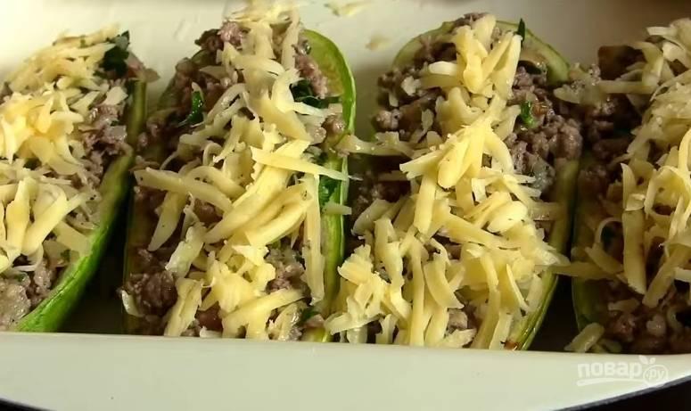 6. Выложите начинку в кабачки, сверху присыпьте сыром. Запекайте 20 минут в духовке при температуре 180 градусов.