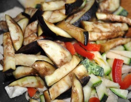 Затем выложите на сковороду промытые кусочки баклажана, цуккини и болгарский перец. Перемешайте и обжаривайте 2 минуты.