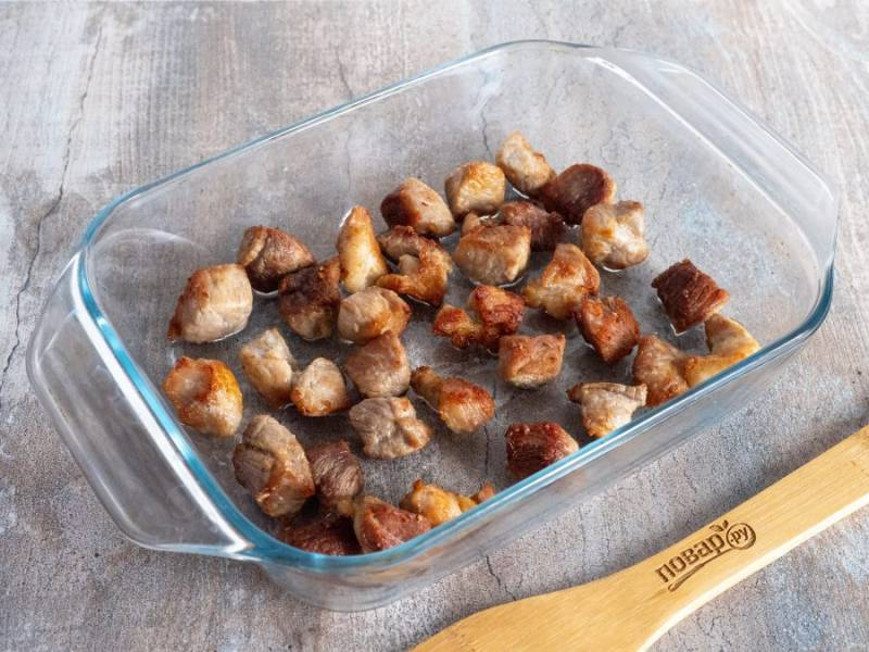 Всё будем готовить на одной сковороде. Сначала в небольшом количестве растительного масла обжарьте кусочки мяса, посолите по вкусу и выложите в форму для запекания.