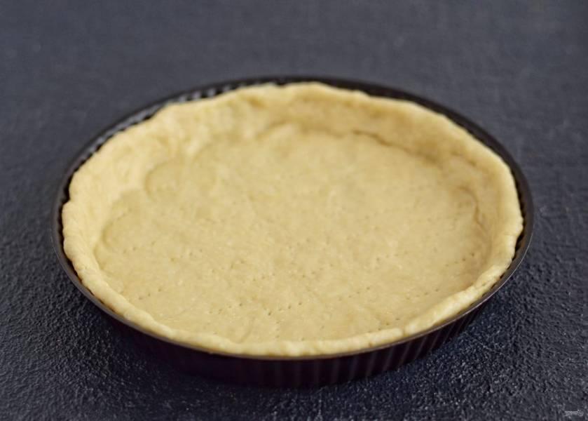 Раскатайте тесто по диаметру формы для выпечки, затем переложите его. Сформируйте бортики, а вилкой наколите дно.