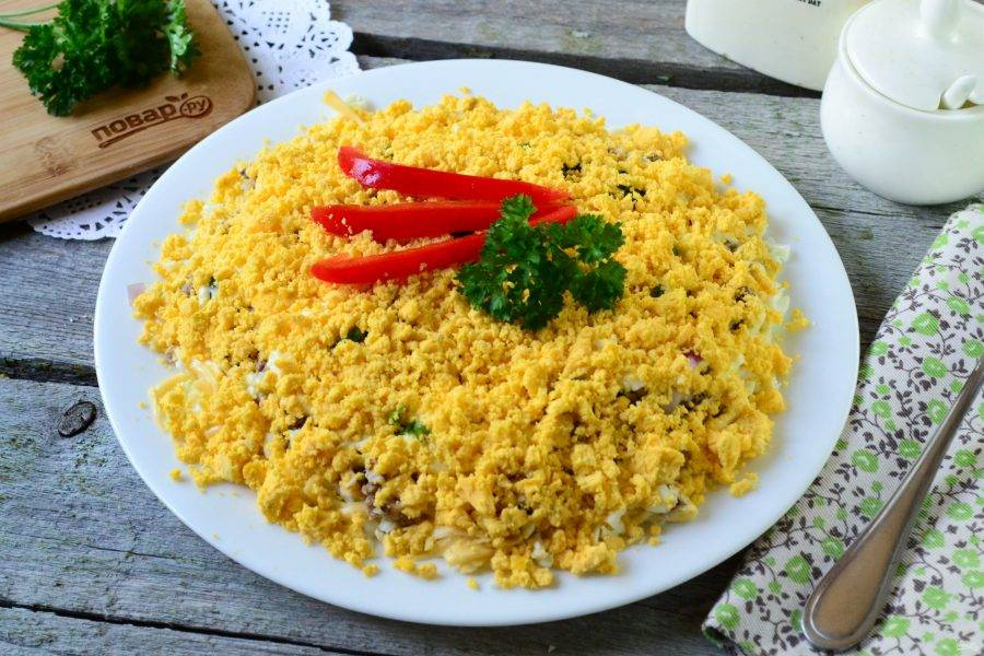 Снова покройте салат сеточкой майонеза. Желтки измельчите вилкой до состояния крошки и покройте верх салата. Украсьте салат по желанию. Приятного аппетита!