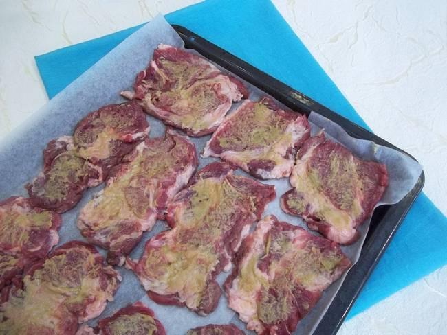 Подготовленный куски свинины выкладываем на противень, который предварительно необходимо застелить бумагой для выпечки. Мясо солим и перчим, равномерно смазываем горчицей.