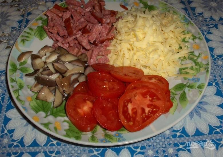 Нарезаем небольшими кусочками колбасу. Томаты нарезаем кружочками. Грибы также мелко нарезаем, а сыр трем на терке.