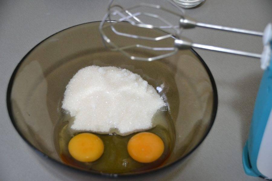 В глубокую миску вбейте два яйца и всыпьте сахар, взбейте до пышности.