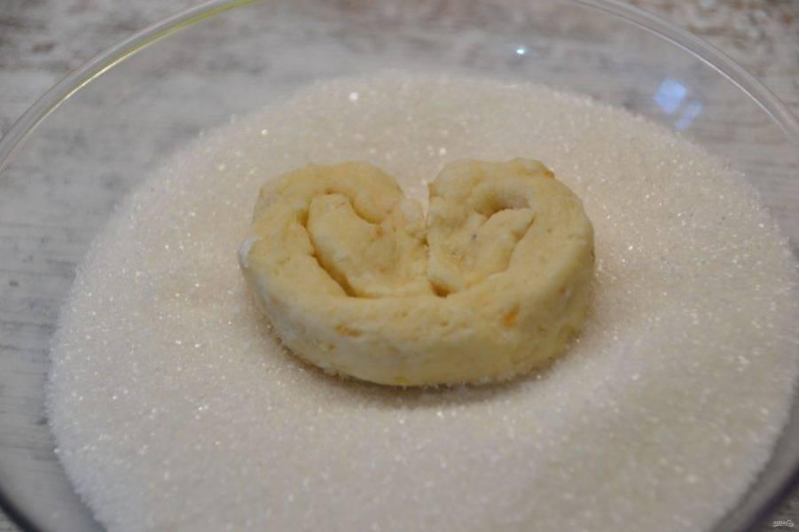 Нарежьте тесто на кусочки, придайте форму сердечка, обмакните в сахар.