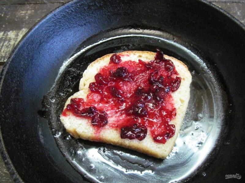 Ломтик хлеба выложите в сковороду и смажьте клюквенным соусом.