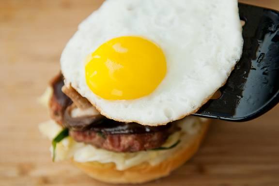 На котлету положите немного грибов, яйцо и накройте верхней половиной булки. Не откладывая, подавайте на стол.