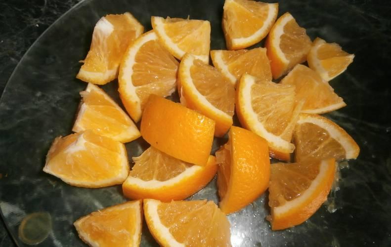 Промываем лимон и апельсин, затем нарезаем фрукты дольками, удаляя косточки.