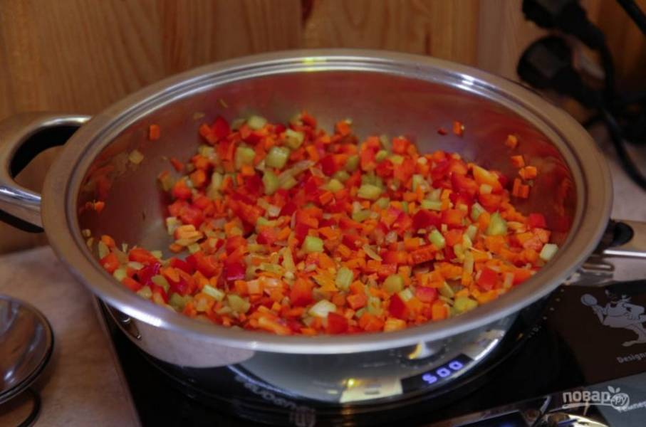 Все остальные овощи вымойте и обсушите. Очистите перец от семечек, лук от шелухи, морковь от кожуры. Нарежьте все овощи кубиками. Влейте в сковороду оливковое масло и обжарьте на нем овощи до полуготовности с веточкой розмарина.