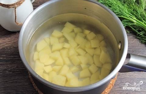 Чистим и нарезаем небольшими кубиками картофель. Дальше заливаем его литром воды и варим до полуготовности.