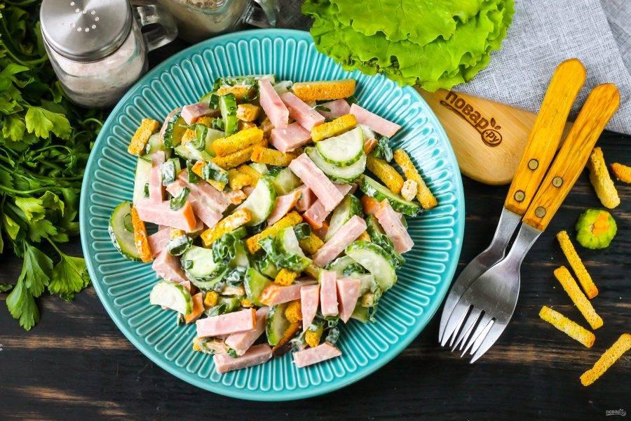 Выложите салат с кириешками и колбасой на тарелки и подайте к столу сразу же после его приготовления, пока овощи не выпустили сок.