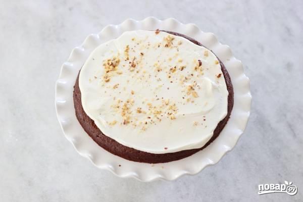 9. Можно приступать к сборке тортика. Выложите корж, смажьте его кремом и присыпьте измеленными орешками.