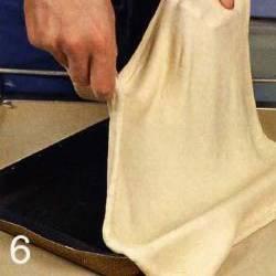 Нагреть духовку до 200 °С. Противень смазать маслом. Тесто раскатать в тонкий блин, уложить на противень, руками сделать бортики. Выложить на тесто смесь из лука ровным слоем. Сверху начинки уложить решеткой рыбу, нарезанную тонкими полосками. В центр каждого ромба выложить маслину. Выпекать пол часа.