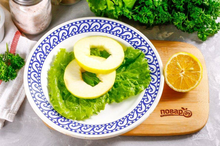 Листья свежего салата промойте в воде, просушите бумажным полотенцем и выложите на тарелку. Яблоко промойте в воде, нарежьте кружочками толщиной 0,5-1 см. Вырежьте сердцевину из каждого круга. Выложите несколько кругов в центр тарелки на листья салата.