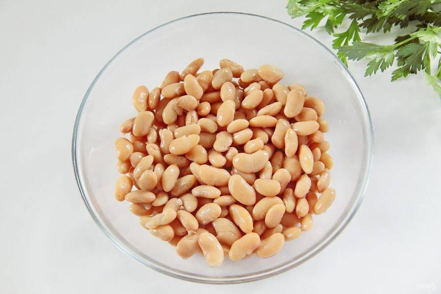 Для начинки насыпьте в миску белую фасоль. Если вы используете консервированную, то предварительно слейте с нее всю жидкость.