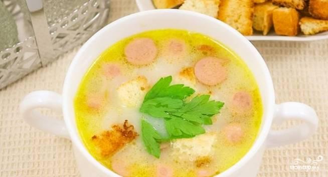 6.Как только картофель будет готов, добавьте в бульон измельченные сосиски и тертый сыр. Все ингредиенты перемешайте. Посолите при необходимости. Проварите еще несколько минут. Подавайте суп, посыпанный зеленью, с гренками. Приятного аппетита.