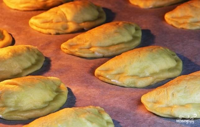 11. Пирожки выложите на застеленный пергаментом противень и выпекайте в разогретой до 180 градусов духовке в течение 25 минут до золотисто-коричневого цвета.