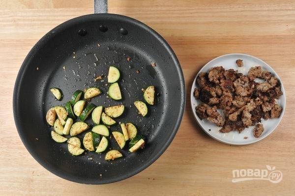3. В это же время обжарьте сосиску в течение 4 минут в небольшом количестве масла, помешивая. Затем уберите фарш. На той же сковороде обжарьте цуккини с чесноком в течение 5 минут, пару раз перевернув.